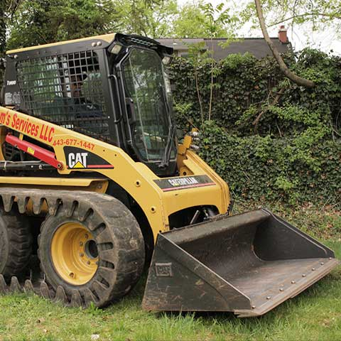 A Caterpillar skid steer, also known as a Bobcat, moves through a grassy lot with a digging bucket attached